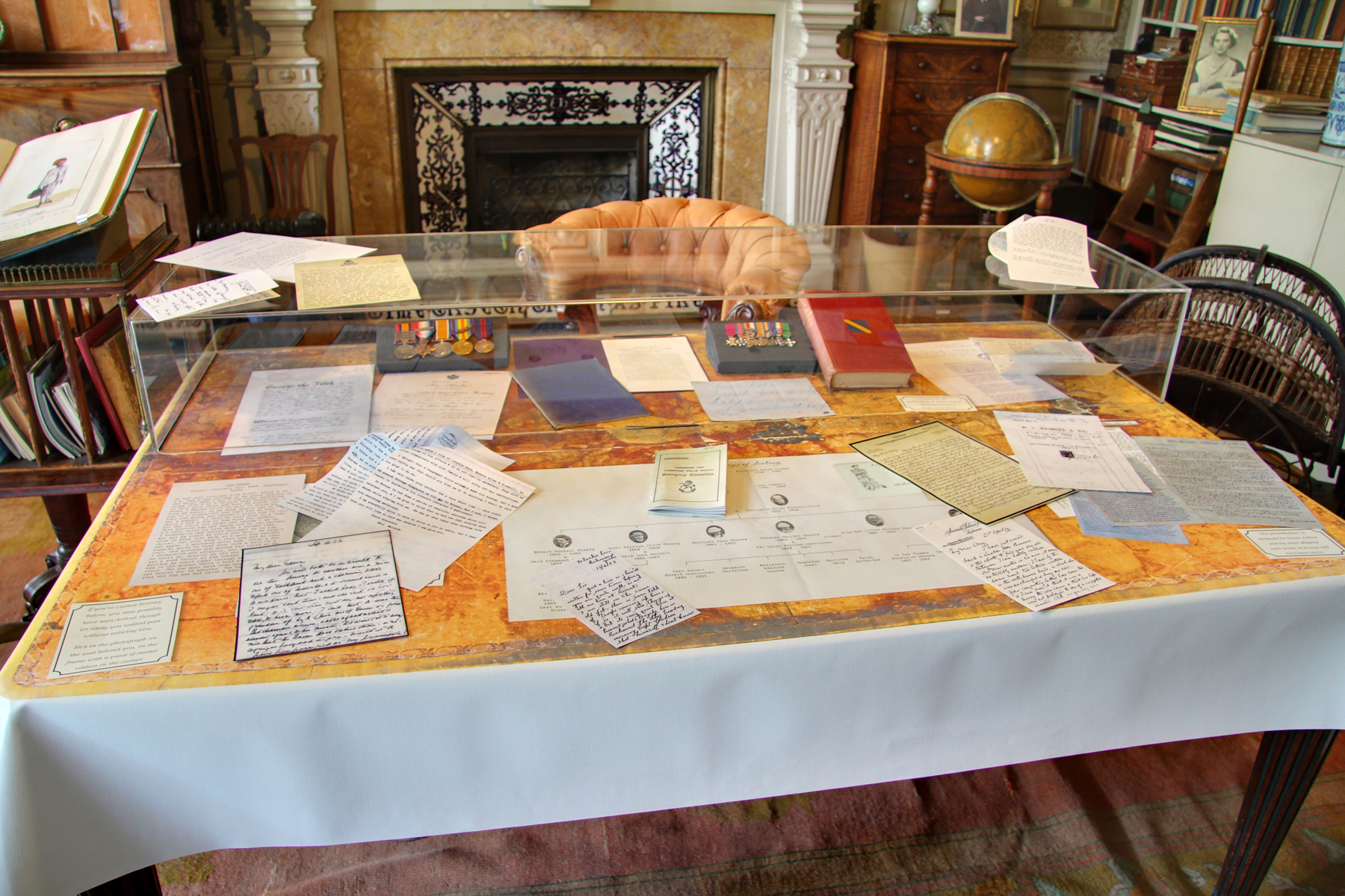 A reproduction of the desk surface in the study is printed with a family tree and reproduction letters, while other papers can be picked up.